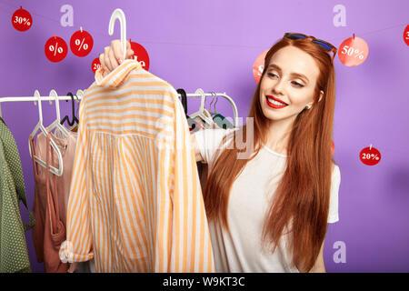 Pelo rojo agradable chica eligiendo una camiseta por su novio. cerrar retrato. aislado sobre fondo azul, tiempo libre, tiempo libre, hobby