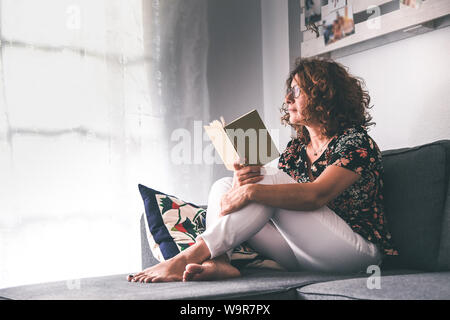 Hermosa niña leyendo un libro sentado en un sofá en casa. Mujer de mediana edad relajarse y disfrutar del tiempo libre de ocio mirando fuera de la ventana. Pensativo
