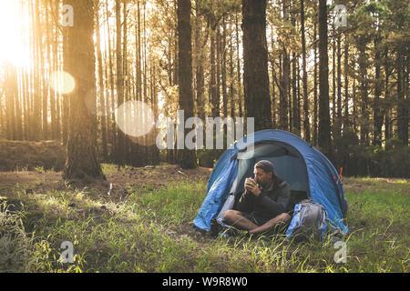 Hermoso macho joven beber una taza de café en la tienda de campaña. Chico turístico disfrutando de la vida al aire libre en la montaña en árboles de fondo y puesta de sol turismo