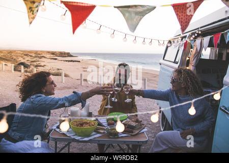 Feliz amigos aclamaciones y beber vino durante el camping vacaciones en la playa con vintage van. La gente divirtiéndose en fin de semana noche de verano con campe