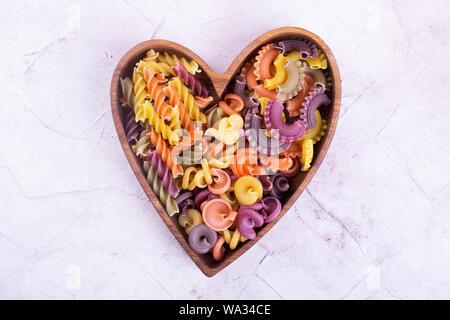 Placa en forma de corazón con pasta. Varios pasta en placa de madera. Me encanta la pasta
