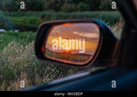 Un coche del espejo retrovisor exterior mostrando una dorada puesta de sol sobre campos verdes detrás en una exuberante pradera