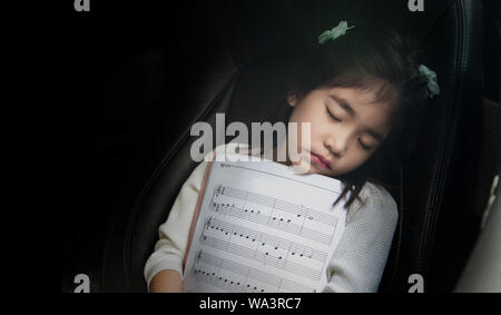 Sueño con kid nota musical en el asiento de coche de amar la música como concepto. Kid pasar tiempo en auto