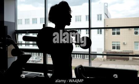 Silueta de una mujer deportiva con un cuerpo de descarga en la ventana haciendo juego de repeticiones ejercicio levantamiento barbell para hombros músculos, espacio de copia