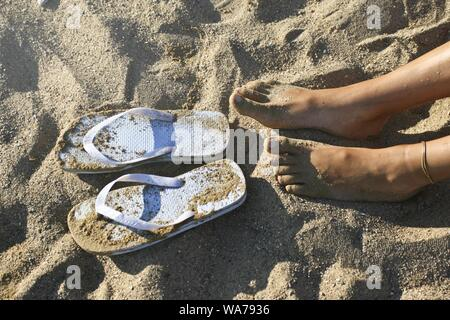 Tiro de pies femeninos cerca de chanclas en la arena