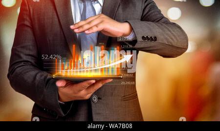 Gente de negocios mantenga una tableta, plan y estrategia y visualizar virtual hologramas de estadísticas, gráficos financieros, títulos y gráficos en una oscura backgr