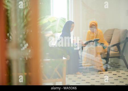 Las mujeres musulmanas jóvenes sentado en el café, beber cócteles deliciosos y discutir los artículos en la revista Foto de stock