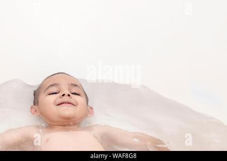 Chico toma un baño. 5-6 años kid tener diversión en el agua en el baño. Espacio de copia