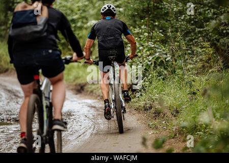 Volver dos ciclistas montando en bicicleta de montaña en el bosque sendero sucio