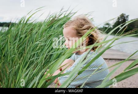 Retrato de una joven muchacha sentada sonriente en la playa en verano