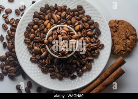 El blanco de la taza de café con café tostado en grano, canela y galletas sobre fondo blanco aisladas desde arriba. Los granos de café en la placa y en la taza.