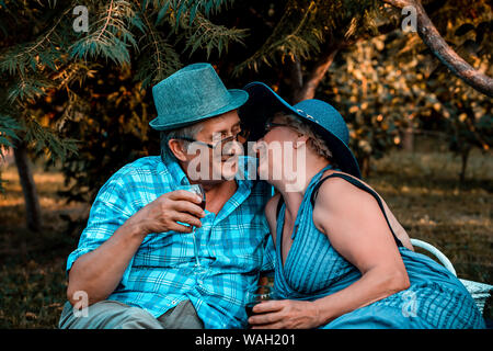 Senior pareja besándose mientras bebiendo vino juntos en un picnic en el parque