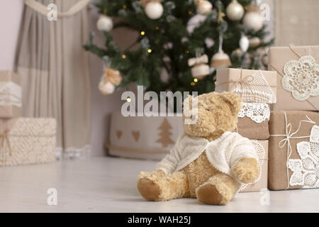 Oso de Peluche Juguetes cerca cerca de la montaña de regalos empaquetados en papel artesanal sobre un fondo difuminado de un árbol de Navidad decorado, el enfoque selectivo
