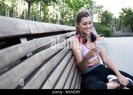 Bastante joven en ropa deportiva con smartphone y sonriendo en un banco