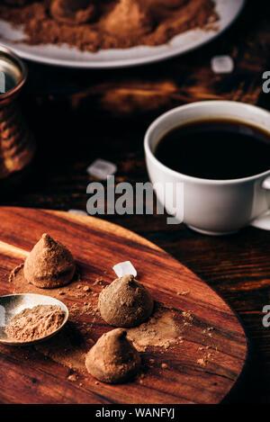 Trufas de chocolate caseras recubiertos de cacao en polvo con café negro