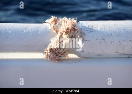 Rotura de cuerda atada con un nudo alrededor de una parte de la vieja paleta de madera en el barco blanco con azul en el fondo de la superficie del mar y espacio de copia