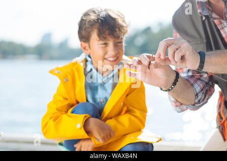 Niño sonriendo mientras abuelo poniendo gusano de gancho de pesca Foto de stock