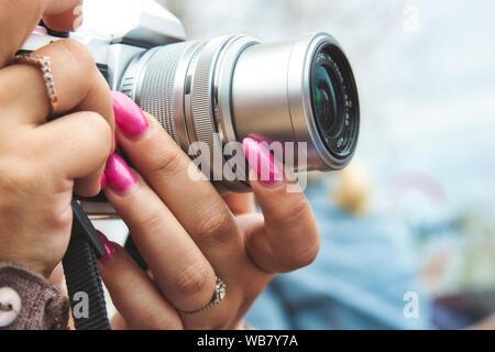 Close-up de una cámara digital utilizado por una mujer con uñas pintadas
