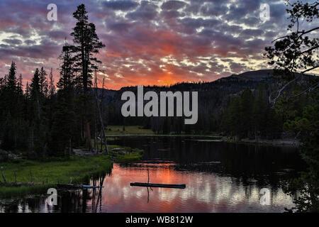 El sol ilumina las nubes de mariposas y reflexiona sobre el lago a lo largo de la SR 150, el Lago Espejo Scenic desviación, en la Cordillera de Uinta, Utah, EE.UU..
