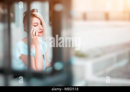 Joven Mujer rubia hablando por teléfono