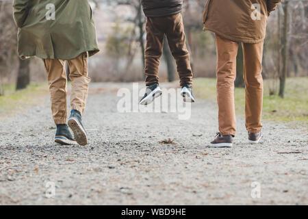 Joven hermosa familia pasear cogidos de la mano por el parque de la ciudad Foto de stock
