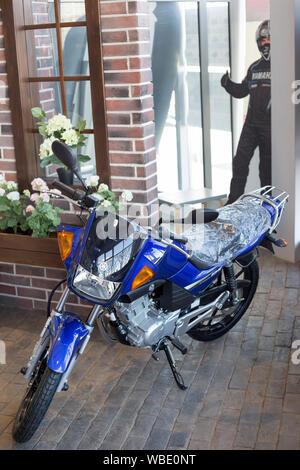 Rusia, Izhevsk - Agosto 23, 2019: motocicleta Yamaha shop. Nueva moto YBR125 está de pie sobre un piso de piedra. La famosa marca mundial.