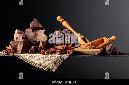 Trufas de chocolate con trozos de chocolate y especias. Chocolate, canela y anís sobre un fondo oscuro. Copie el espacio.