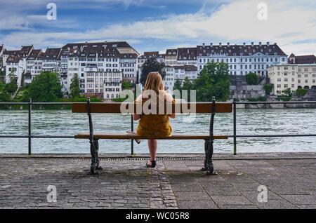 Vista trasera de una mujer sentada en un banco en la ciudad de Río Foto de stock