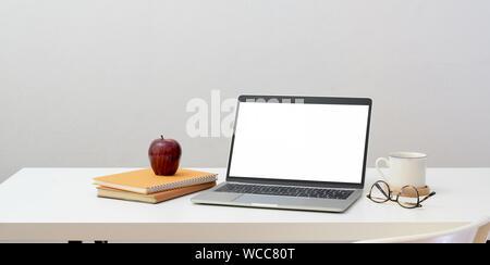 Concepto workplace mínima : abrir el portátil de pantalla en blanco con suministros de oficina y decoraciones