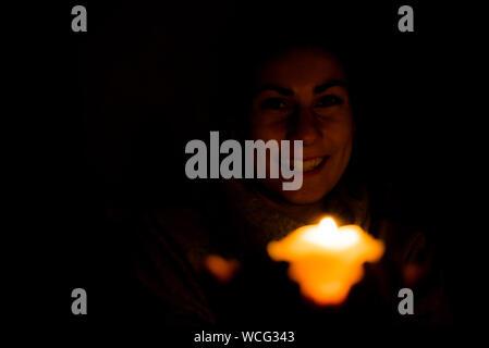 Retrato de mujer feliz celebración vela encendida en el cuarto oscuro Foto de stock