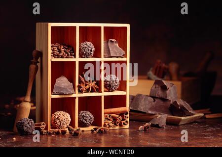 Trufas de chocolate con trozos de chocolate y especias. Chocolate, canela, anís y granos de café en caja de madera.