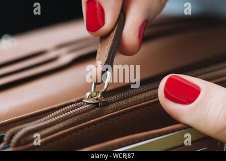 Close-up de la mujer recortada tirando de embrague Bolsa Zipper