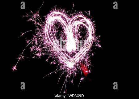 Fuegos artificiales en forma de corazón en la noche