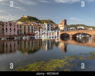 La ciudad medieval de Bosa durante la puesta de sol. Puente y coloridas casas reflejadas en el río temo. Castillo de la ciudad