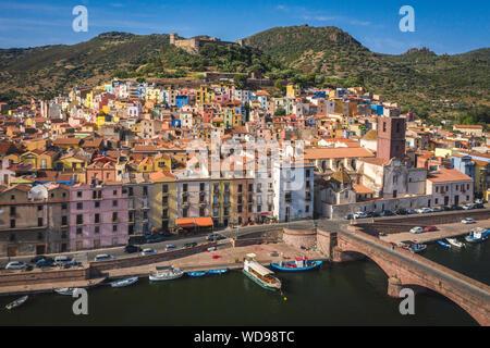 Coloridas casas de ladera de la ciudad medieval de Bosa, Cerdeña, Italia. Mediterráneo hermoso casco antiguo con el castillo en la colina. En abajo, Temo río con bo