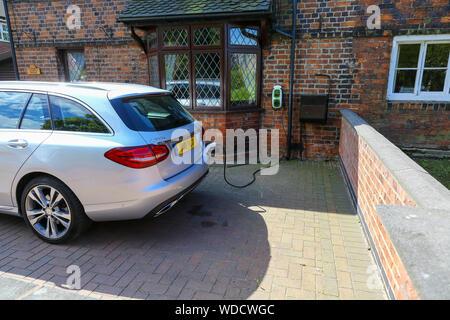 Un Mercedes C350 híbrido eléctrico station wagon está cargado eléctricamente en el camino por un punto de carga doméstica, Staffordshire, Inglaterra, Reino Unido. Foto de stock