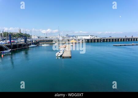 Una escena en Dun Laoghaire Harbour con pequeños yates amarrados a un pontón y el bote salvavidas RNLI en el fondo. Foto de stock