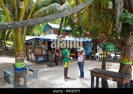 Colombia, la isla de Providencia, Colombia pareja conversando sobre la arena de Rolland's bar, un bar oculto bajo la vegetación tropical en la playa de Manzanillo