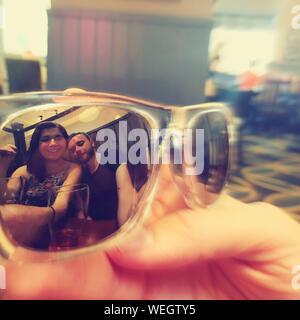 Retrato de pareja sonriente reflexionando sobre gafas de sol Foto de stock