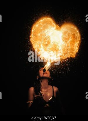 Mujer de soplado de fuegos artificiales en forma de corazón en la noche