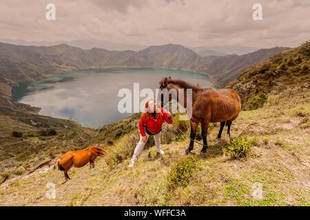 Mujer con caballos en campo contra las montañas Foto de stock