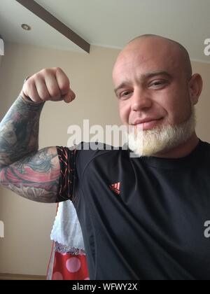 Retrato del hombre maduro sonriente con tatuajes en el brazo flexionando los músculos contra la pared