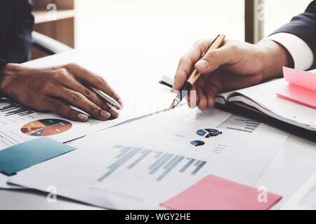 Recorta las manos de gente de negocios discutiendo los datos en Office