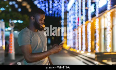 Hombre negro sonriente Celebración último smartphone, paseos por la ciudad de noche Foto de stock