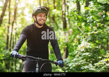 Alegre ciclista macho en un bosque de montaña en bicicleta