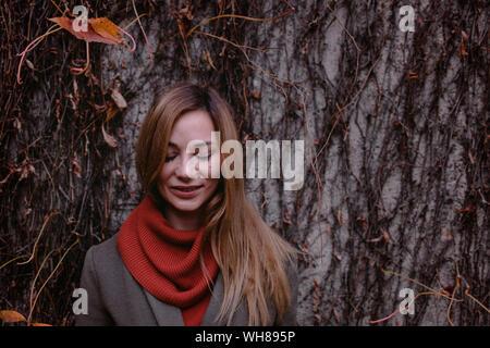 Retrato de mujer sonriente con los ojos cerrados en otoño