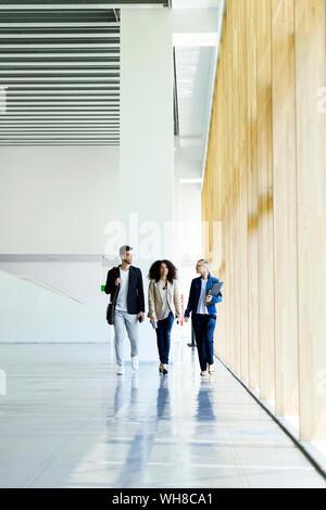 Jóvenes empresarios caminar y hablar en un pasillo