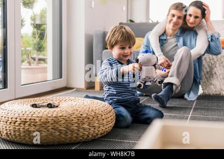 Los padres viendo hijo, jugando con robot de juguete Foto de stock