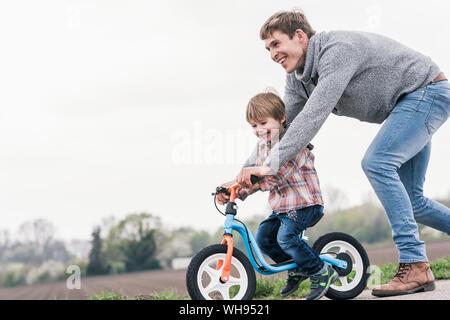 Padre cómo enseñar a su hijo a andar en bicicleta, actividades al aire libre Foto de stock