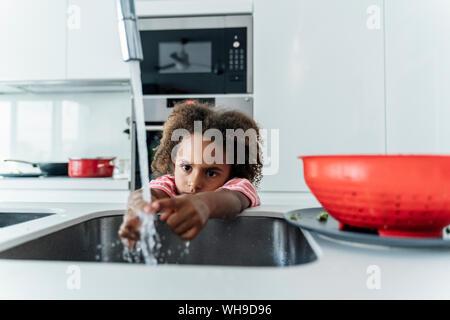 Chica lavando sus manos en el lavabo de la cocina